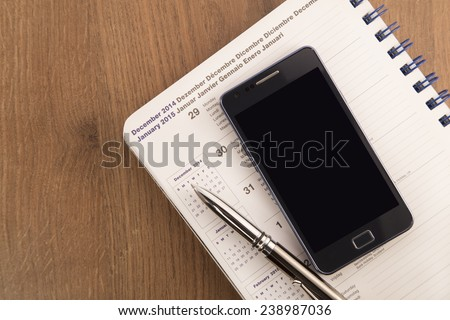 Mobile phone, pen and agenda on wooden background - stock photo