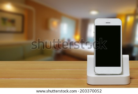 Mobile phone with dock station on blur bedroom background. - stock photo