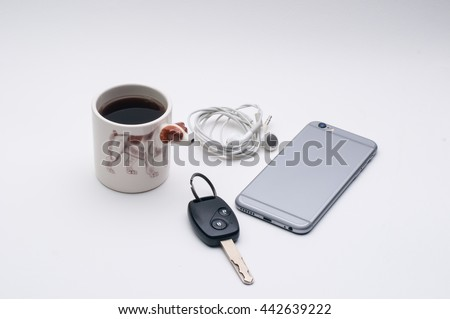 mobile phone with headphone, car key, cup of coffee, Jack Russel dog side of coffee cup, on white table - stock photo