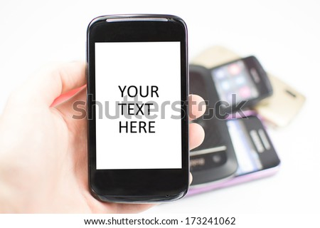 Mobile phone with white screen and space for text, with more mobile phones in the background.  - stock photo
