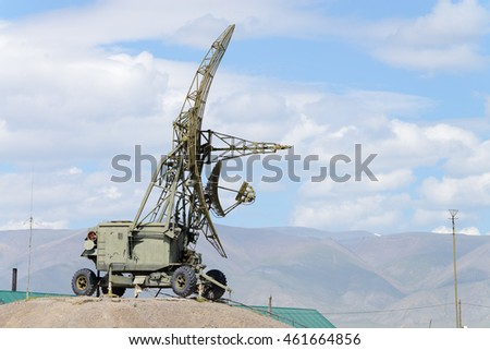 mobile radar set on a hill on a background of mountains and clouds