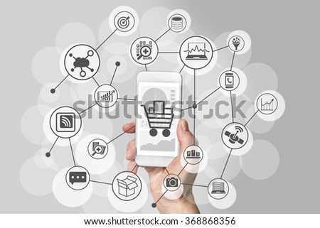 Mobile shopping experience with hand holding smartphone to connect to online shops to purchase consumer goods - stock photo