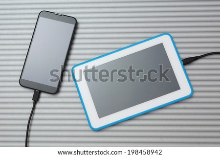 mobile smart phone and tablet pc charging on silver desk - stock photo