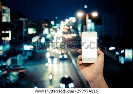 Mobile smart phone behind a blur of traffic. - stock photo