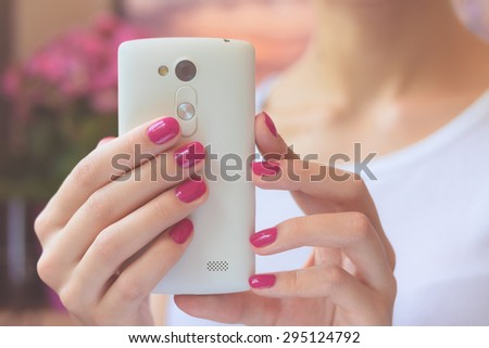 Mobile smart phone in female hands with a pink manicure on the background of pink flower and girl in a white T-shirt. Soft light. - stock photo