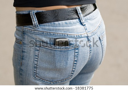Mobile telephone in back pocket of jeans.
