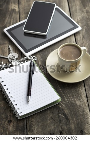 Mobile workplace with tablet PC, phone and cup of coffee on rustic wooden table. - stock photo