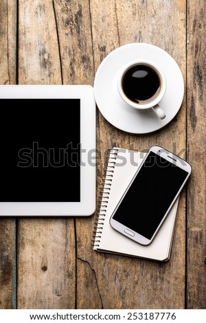 Mobile workplace with tablet PC, phone and cup of coffee on rustic wooden table. Top view mock-up image - stock photo