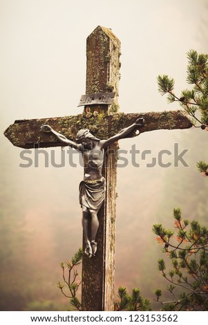 Moble photography lo-fi styled image of lichens covered figure of Christ on the Cross at the Crucifixion standing outdoors amonst pine branches against a misty fall forest backdrop - stock photo