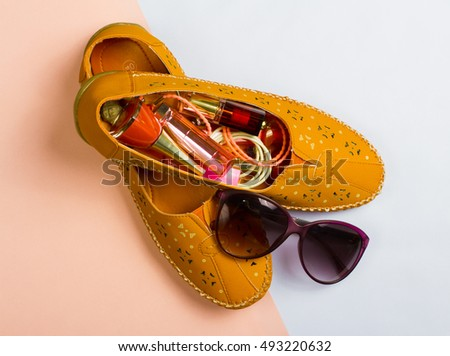 Moccasins and makeup on abstract background.