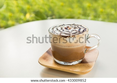 Mocha coffee (also called Caffe Mocha) with wooden saucer on white table. Interior coffee shop. Main ingredients of mocha is chocolate, espresso, hot milk (Selective focus and shallow depth of field) - stock photo