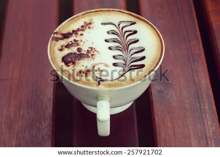 Mocha in white coffee cup in the Coffee Shop, retro and vintage tone - stock photo