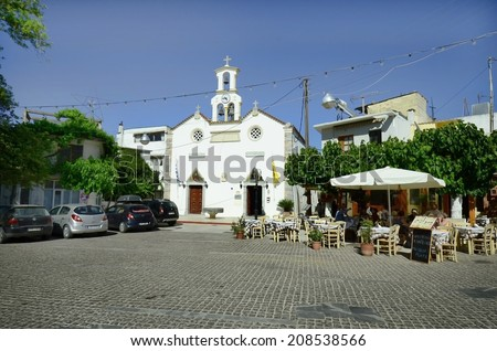 MOCHOS, GREECE - MAY 23: Unidentified people in street restaurant on main square and orthodox church in the tiny mountain village in Crete, on May 23, 2014 in Mochos, Greece
