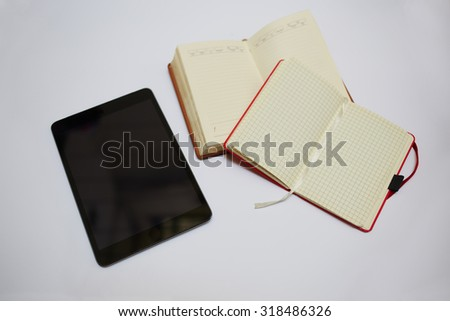 Mock up composition with digital tablet and notebooks lying on white background table , blank screen touch pad and open writing-pads with copy space for text