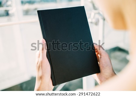 Mock up of black book in hands - stock photo