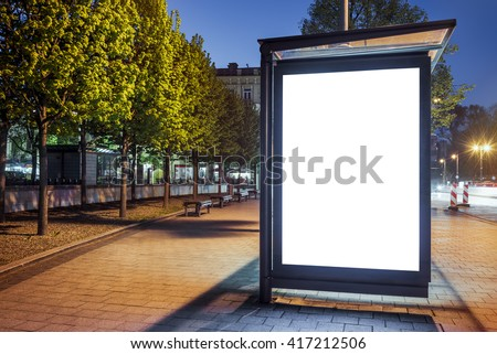 Mock up of blank white vertical light box on a bus stop in a city at night - stock photo