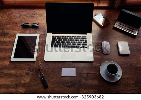 Mock up of modern freelance desktop with accessories and distance work tools, blank screen laptop computer and digital tablet, sunglasses, cup of coffee, touch pad and hard drive, business workspace - stock photo