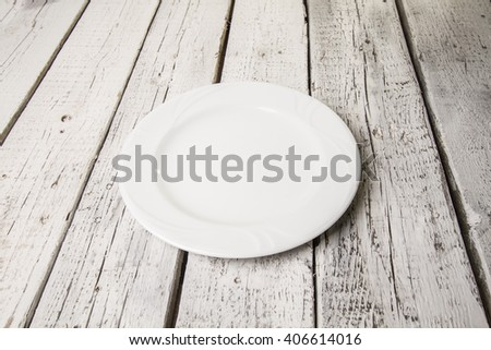 Mock up white plate on white wooden table - stock photo