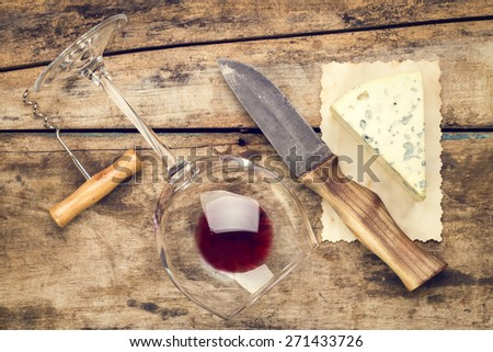 Mock up wine and cheese set. Overturned glass with red wine and piece of cheese with mold. Warm color toned image - stock photo