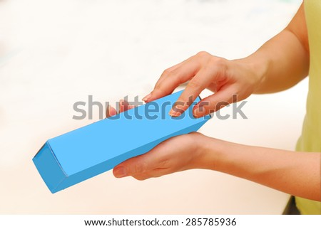 mockup hands holding a blue box ( concept presentation of household packaging )