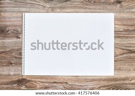 Mockup of open album with blank white page on wooden background. Gorizontal orientation, top view. - stock photo