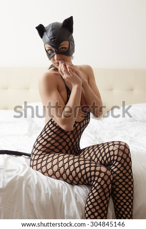 Model advertises catwoman costume in hotel room - stock photo