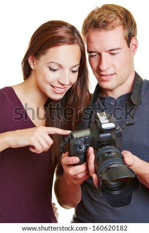 Model and photographer checking their new images in the camera display - stock photo