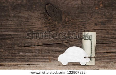 model car with silver chain over a lot of dollar bills on old wood background. space for your text