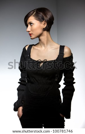 model fashion woman in black with bare shoulders and red lips posing on a white background - stock photo