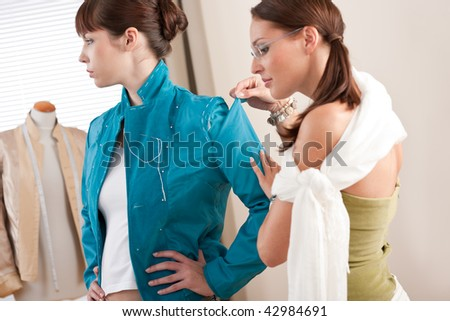 Model fitting by professional female fashion designer studio - stock photo