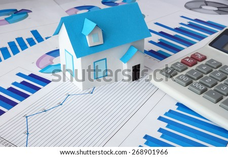 Model  house for sale and graphs. Real estate concept. - stock photo