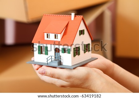 Model house in woman's hand, boxes in the background