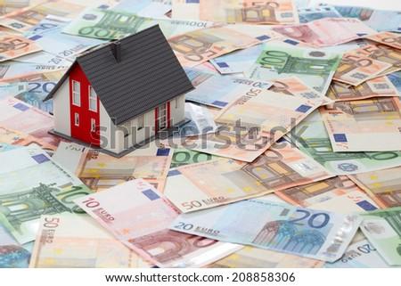 Model house on euro banknotes background - stock photo