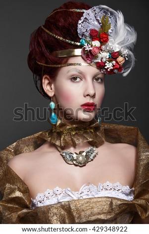 Model in baroque gold attire. - stock photo