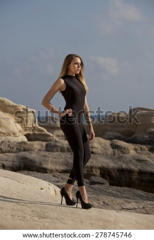 Model in black catsuit and spiked heels posing by the sunset on the rocks