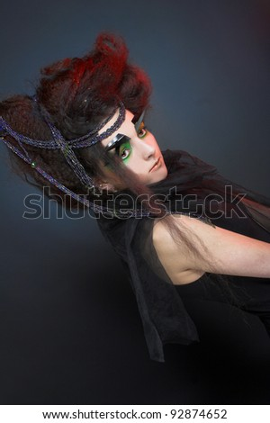 Model in black dress and  with artistic visage and hairstyle