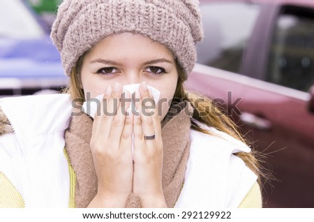 Model in outdoors environment with beenie and scarf blowing her nose