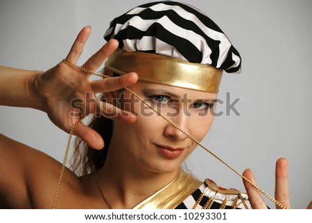 Model in stripy black-and-white cap stares and holds in spread hands gold chain, close-up, portrait - stock photo