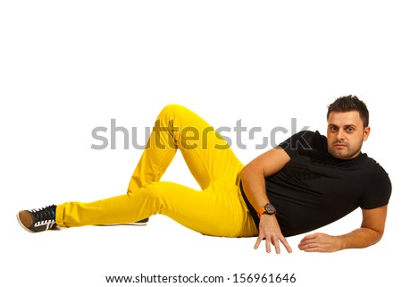 Model man in black t-shirt and yellow pants laying on floor - stock photo