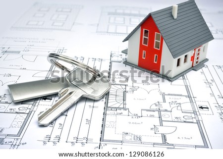 model of a house and key ring on a blueprint - stock photo