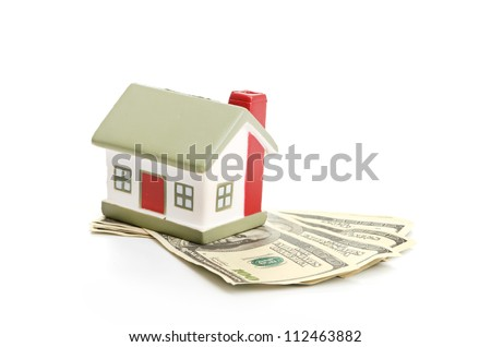 Model of a house lying on some banknotes
