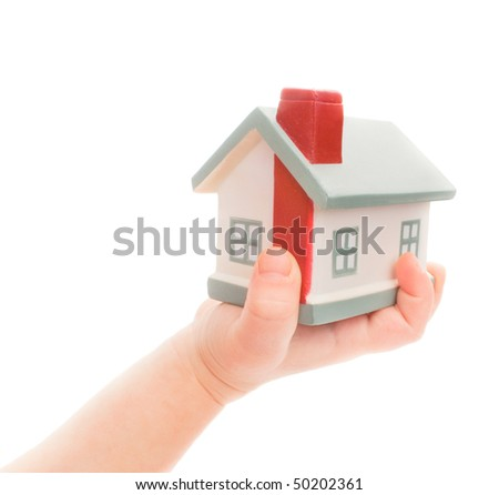 Model of a house on chilsd's hand isolated on white - stock photo