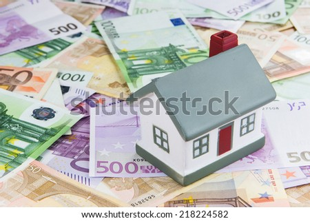 model of a toy house placed on Euro banknotes. Concept for real estate costs, prices, buy or rent a house, hypothecary credit, interest - stock photo