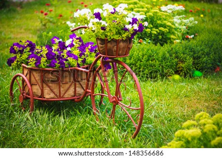 Model of an old bicycle equipped with basket of flowers / Bicycle in a garden - stock photo
