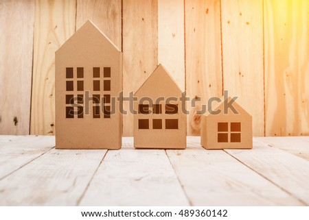 model of cardboard house on wooden floor and background. house building, loan, real estate or buying a new home concept.
