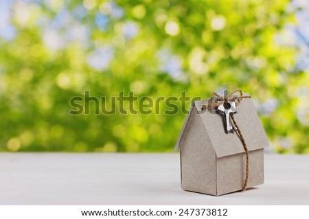 model of cardboard house with a bow of twine and key against green bokeh background. house building, loan, real estate or buying a new home concept.  - stock photo