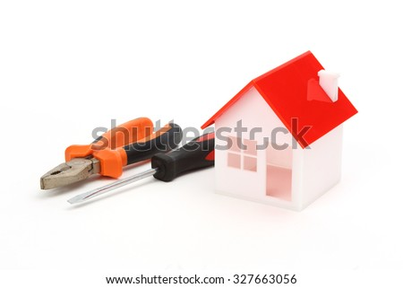 model of house and tools over white