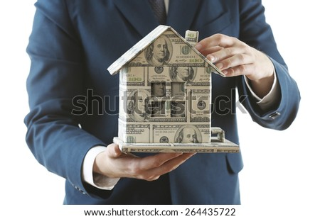 Model of house made of money in male hands isolated on white background - stock photo