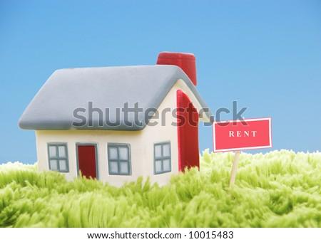 Model of house on blue sky background - stock photo