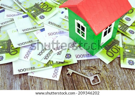 Model of house on money / Image of a model house standing on Euro banknotes - stock photo
